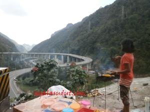 Pedagang jagung bakar menghadap Jembatan Kelok 9. 16 Agustus 2014