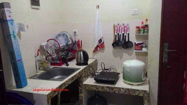 Dapur mini dengan piring, gelas dan teman-teman. Plus kompor induksi, kettle listrik, dan rice cooker.
